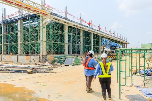 Une équipe de chantier ou une ouvrière portant un casque discutent lors de la construction d'un échafaudage