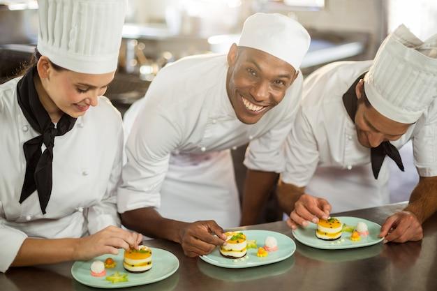 Équipe de chefs finissant les assiettes à dessert
