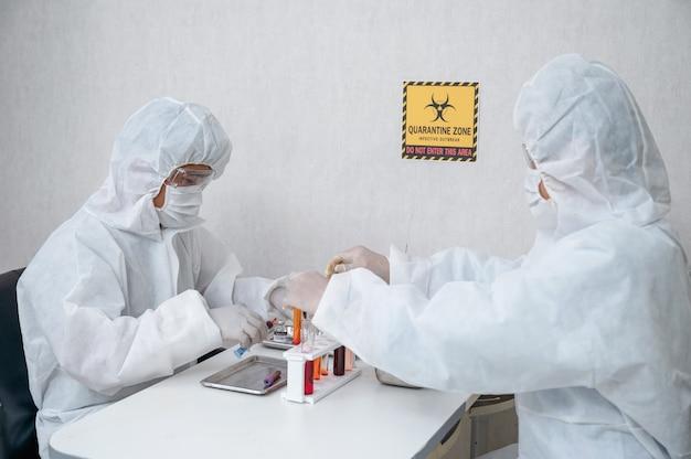 Équipe de chercheurs en combinaison de protection médicale inventant et recherchant un médicament antiviral