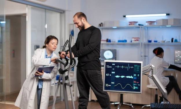 Équipe de chercheurs en médecine surveillant la vo2 des sports de performance masculins portant un masque en cours d'exécution. docteur en sciences de laboratoire mesurant l'endurance d'un sportif pendant que l'analyse ekg s'exécute sur un écran d'ordinateur en laboratoire.