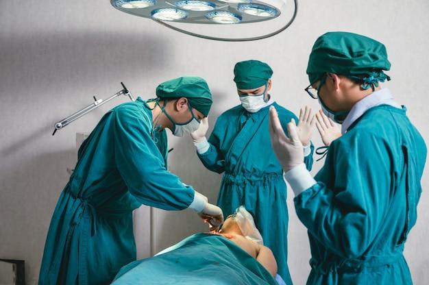 Équipe de chirurgiens asiatiques en blouse chirurgicale effectuant une intervention chirurgicale un patient gravement blessé en salle d'opération à l'hôpital