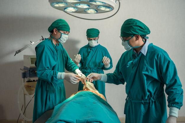 L'équipe de chirurgiens asiatiques effectuant une intervention chirurgicale et passant des ciseaux chirurgicaux sur un patient blessé en salle d'opération à l'hôpital
