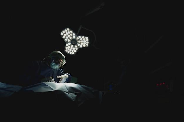 Équipe de chirurgiens au travail sur la salle d'opération à l'hôpital. dans ton sombre.