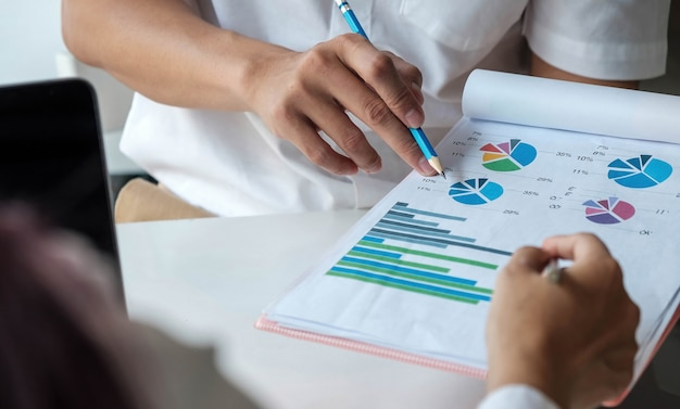 Équipe commerciale analysant les tableaux et graphiques de revenus avec un ordinateur portable moderne. vue de dessus en gros plan sur l'analyse commerciale et le concept de stratégie.