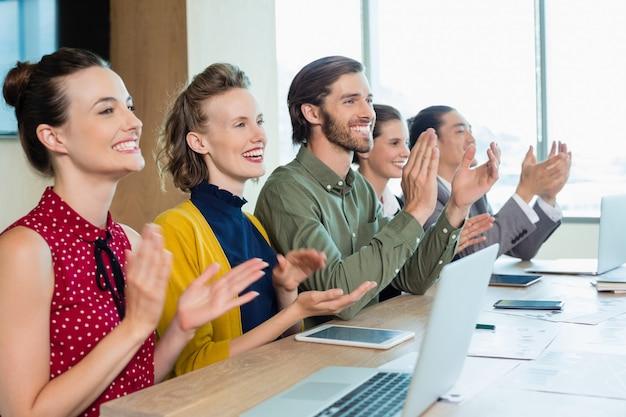 L'équipe commerciale applaudissant lors de la réunion dans la salle de conférence