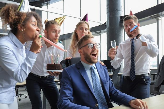 Équipe commerciale célébrant l'anniversaire d'un collègue dans le bureau moderne.