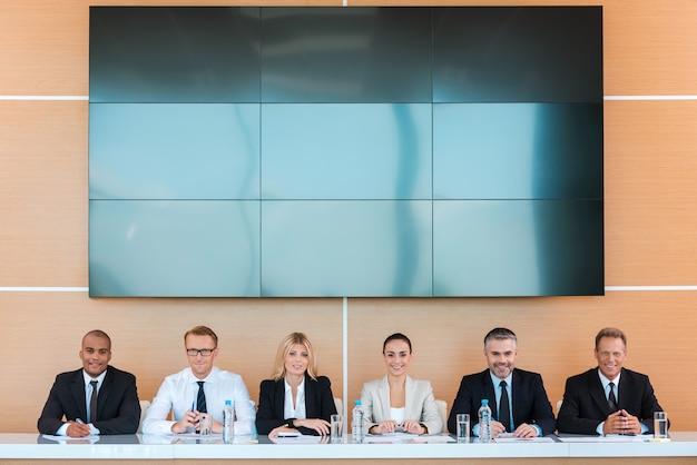 Équipe commerciale confiante. groupe d'hommes d'affaires assis ensemble à la table et souriant avec un grand écran sur la tête