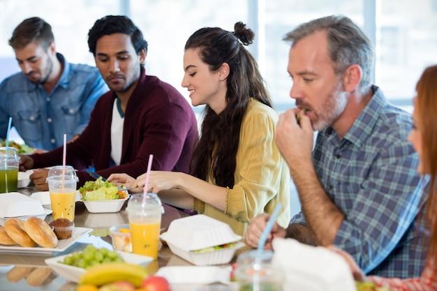 Équipe commerciale créative ayant un repas au bureau