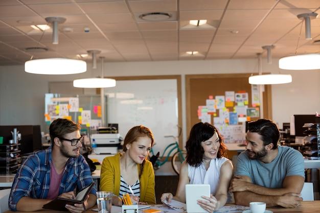 Équipe commerciale créative discutant sur tablette numérique au bureau au bureau