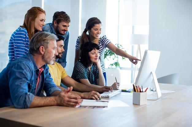 Équipe commerciale créative discutant tout en travaillant ensemble sur un ordinateur de bureau au bureau