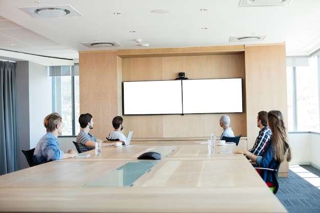 L'équipe commerciale créative participant à un appel vidéo dans la salle de conférence au bureau