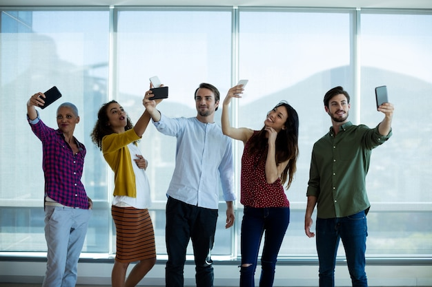 Équipe commerciale créative prenant selfie avec téléphone portable au bureau