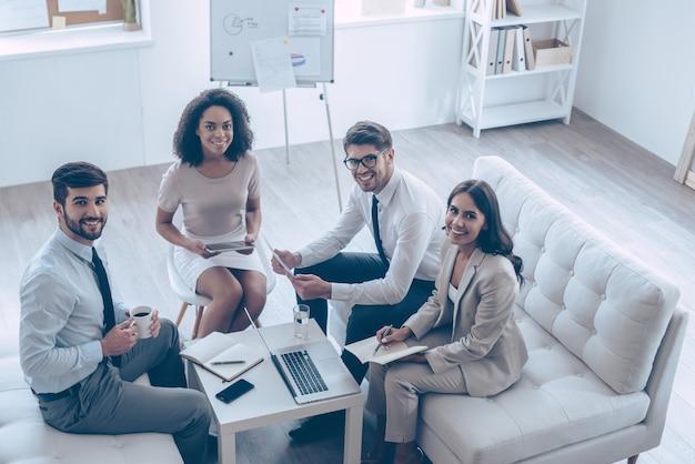 Équipe commerciale créative. vue de dessus du groupe de quatre jeunes regardant la caméra avec le sourire alors qu'il était assis sur le canapé au bureau