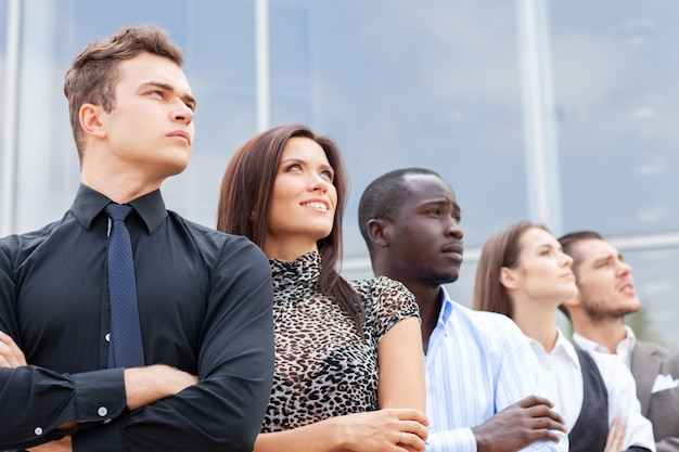 Équipe commerciale debout dans une rangée au bureau et regardant vers le haut
