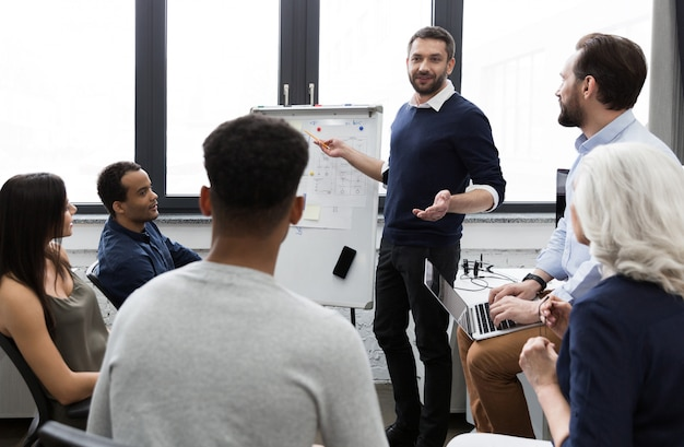 Équipe commerciale discutant de leurs idées tout en travaillant au bureau