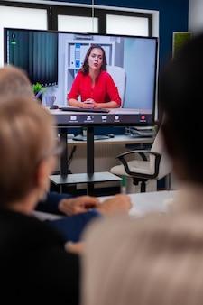 Équipe commerciale diversifiée ayant une réunion vidéo discutant en ligne avec le directeur exécutif à distance
