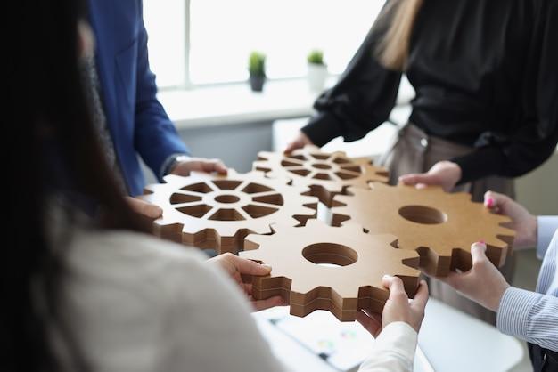 Une équipe commerciale efficace relie les engrenages en bois en un seul