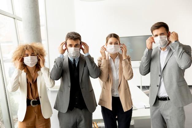 L'équipe commerciale enlève leur masque facial de protection et en regardant la caméra dans le bureau