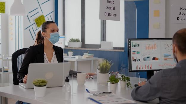 Équipe commerciale examinant la stratégie financière dans une entreprise de bureau portant un masque facial pour prévenir l'infection par covid19 tout en gardant une distance sociale. collègues tapant sur ordinateur pour projet marketing