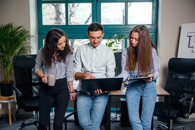 Équipe commerciale de jeunes architectes ou designers créant un nouveau projet tout en travaillant dans le bureau moderne et élégant avec grande fenêtre.