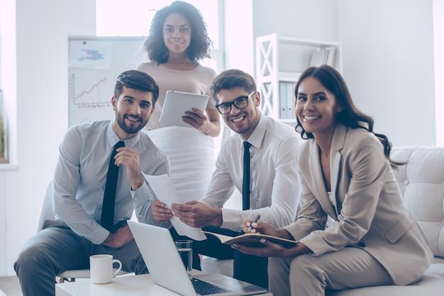 Équipe commerciale joyeuse. groupe de quatre jeunes regardant la caméra avec le sourire alors qu'ils étaient assis sur le canapé au bureau