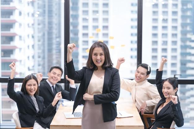Équipe commerciale joyeuse joie à atteindre la cible en réunion.