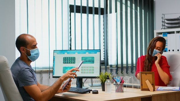 Equipe commerciale avec masques de protection respectant la distanciation sociale à l'aide de plexiglas. les pigistes travaillant dans un nouveau lieu de travail de bureau normal parlent d'écriture sur le presse-papiers en recherchant sur ordinateur.