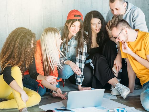 Équipe commerciale millénaire travaillant ensemble. groupe de jeunes diversifié assis sur le sol.