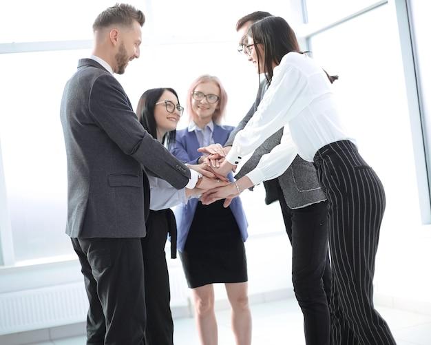 Équipe commerciale montrant son unité en se tenant debout au bureau. le concept de travail d'équipe