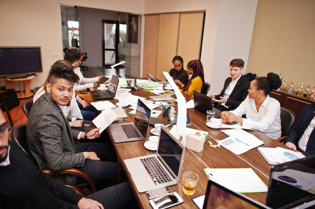 Équipe commerciale multiraciale abordant la réunion autour de la table de réunion