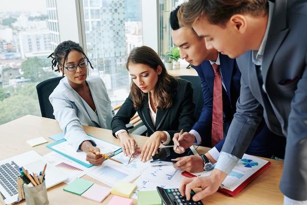 Équipe commerciale pointant sur le rapport financier
