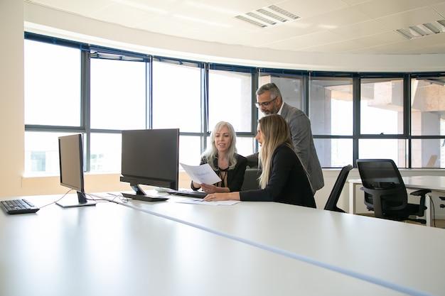 Équipe commerciale positive discutant du rapport, assis à la table de réunion avec moniteur, tenant à la recherche de documents. réunion d'affaires ou concept de travail d'équipe