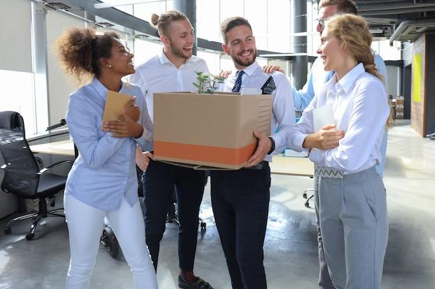 L'équipe commerciale rencontre un nouvel employé dans un grand bureau moderne.
