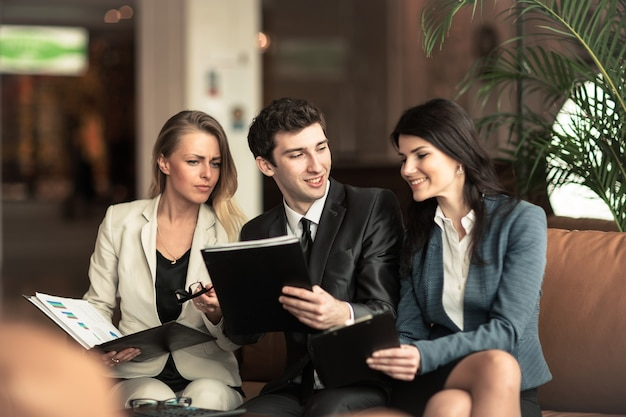 Équipe commerciale réussie discutant des documents financiers assis sur le canapé