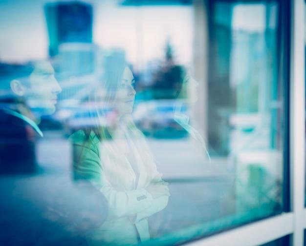 L'équipe commerciale réussie se tient devant une fenêtre dans un moderne