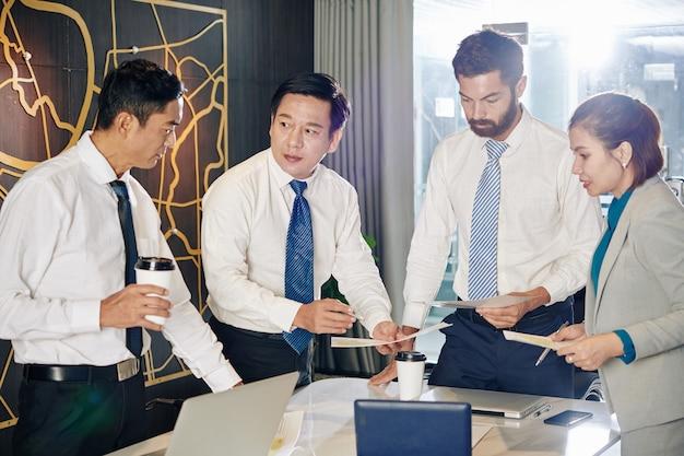 L'équipe commerciale s'est réunie dans la salle de réunion pour discuter des rapports et des documents financiers et essayer de trouver le meilleur moyen de surmonter la crise financière