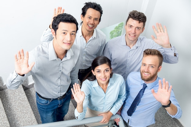 Équipe commerciale souriante agitant sur l'escalier de bureau