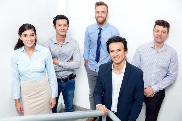 Équipe commerciale souriante debout sur l'escalier de bureau
