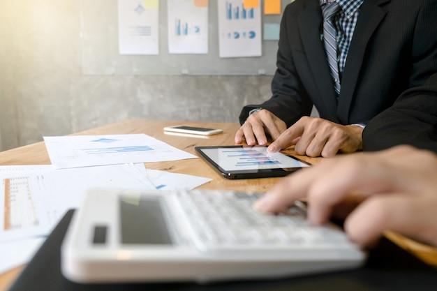 Équipe commerciale utilisant une calculatrice analysant les documents de données sur la tablette numérique