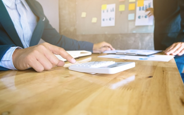 Équipe commerciale utilisant une calculatrice analysant les documents de données et utilisant la calculatrice