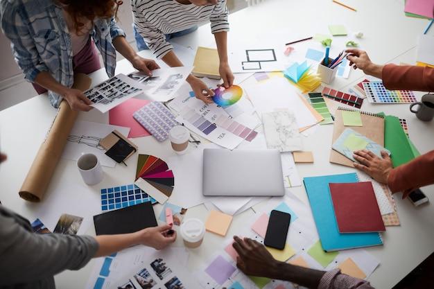 Équipe de concepteurs créatifs discutant de la production sur table