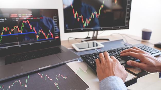 Équipe de courtiers ou de commerçants parlant de forex sur plusieurs écrans d'ordinateur de la bourse