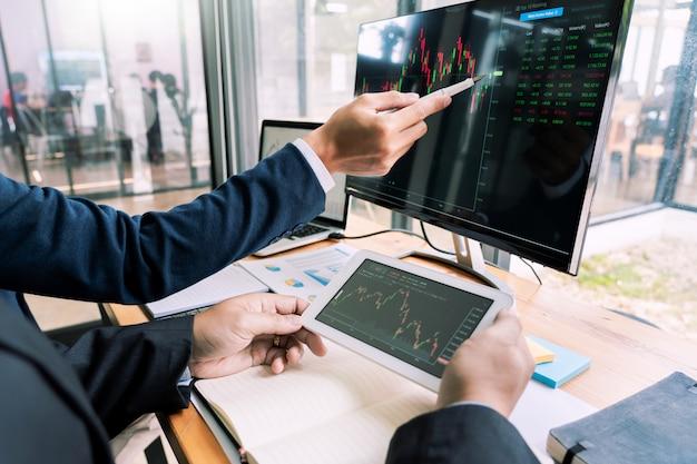 Équipe de courtiers en valeurs mobilières discuter avec des écrans d'affichage analyser des données