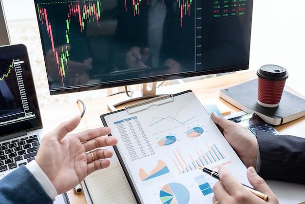 Équipe de courtiers en valeurs mobilières discuter avec des écrans d'affichage analyser des données.