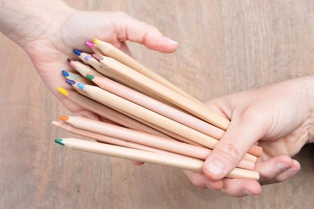 Équipe de crayons souriants colorés. relais, compétition. isolé sur blanc