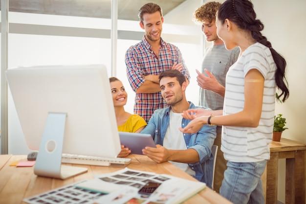 Équipe de création d'entreprise discutant sur une tablette
