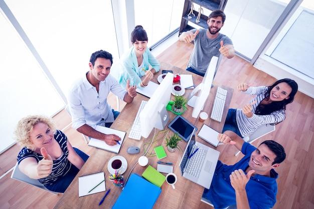 Équipe de création d'entreprise gesticulant pouce en l'air lors d'une réunion