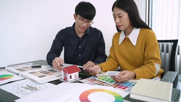 Équipe créative analysant et brainstorming planning sur un projet commun dans le studio de design coworking space.