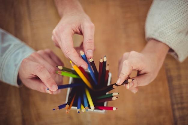 Équipe créative choisissant des crayons de couleur différente