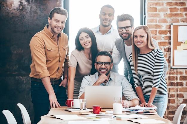 Équipe créative parfaite. groupe de six jeunes joyeux regardant la caméra avec le sourire tout en se penchant vers la table au bureau